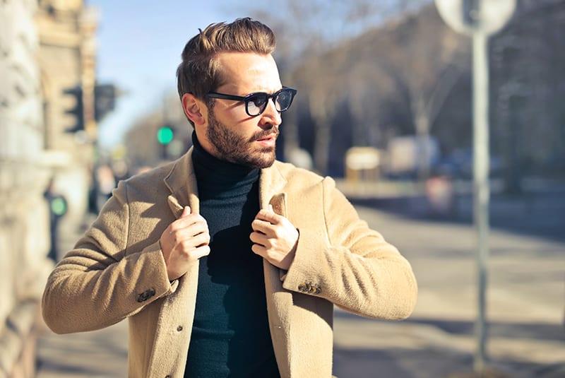 Ein Mann mit Brille und brauner Jacke geht auf dem Bürgersteig spazieren