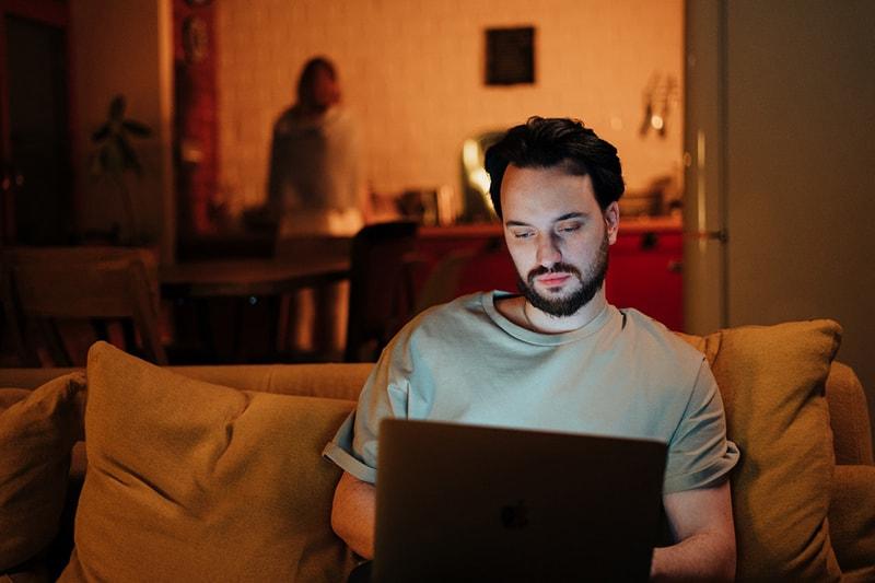 Ein Mann benutzt einen Laptop, der auf der Couch sitzt, während eine Frau hinter ihm in der Küche steht