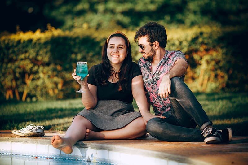 Ein Mann neigt den Kopf zu einer lächelnden Frau, während er in der Nähe des Schwimmbades sitzt