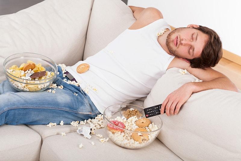 Ein Mann schläft auf der Couch in einem Durcheinander von Junk Food