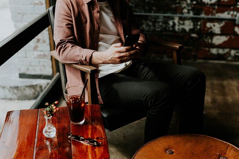 Ein Mann schreibt eine Nachricht auf das Smartphone, während er etwas trinkt