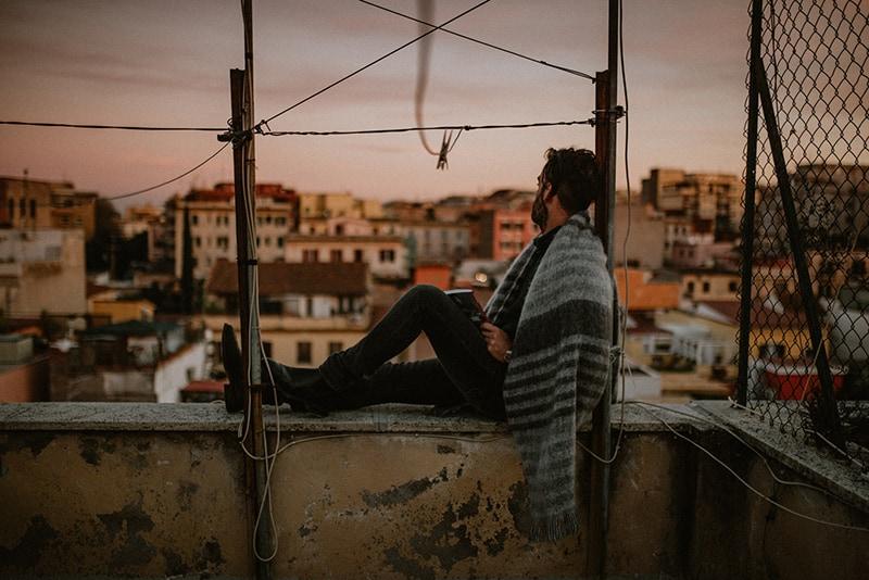 Ein Mann, der alleine oben auf dem Gebäude sitzt und weit weg schaut