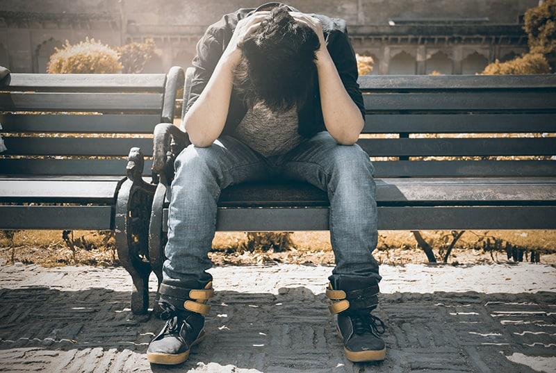 Ein Mann sitzt auf der Bank und schaut nach unten, während er seinen Kopf berührt