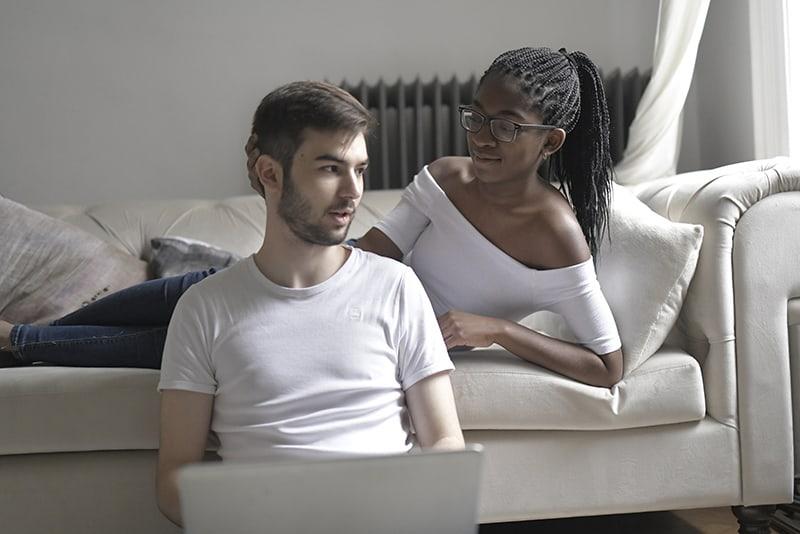 Ein Mann spricht mit einer Frau, die auf dem Sofa liegt