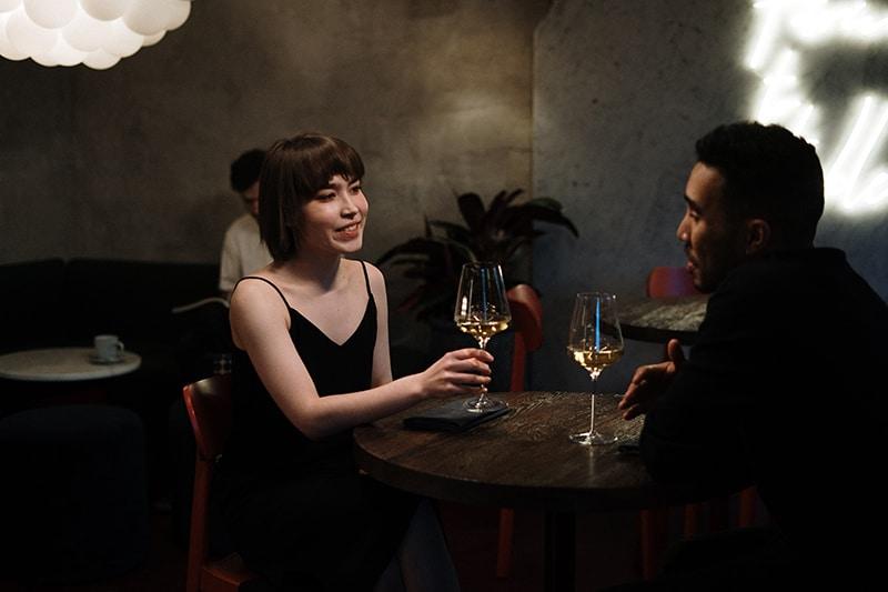 Ein Mann spricht mit einer Frau, während er im Restaurant Wein trinkt
