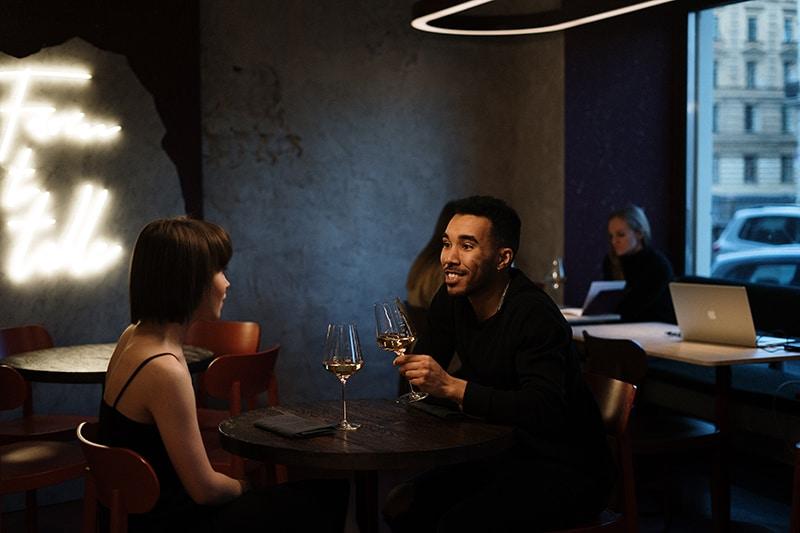 Ein Mann spricht mit einer Frau, während er im Restaurant sitzt und Wein trinkt