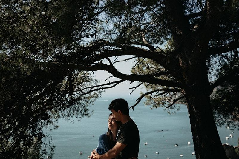 Ein Mann umarmt eine Frau, während er im Wald in der Nähe des Meeres steht