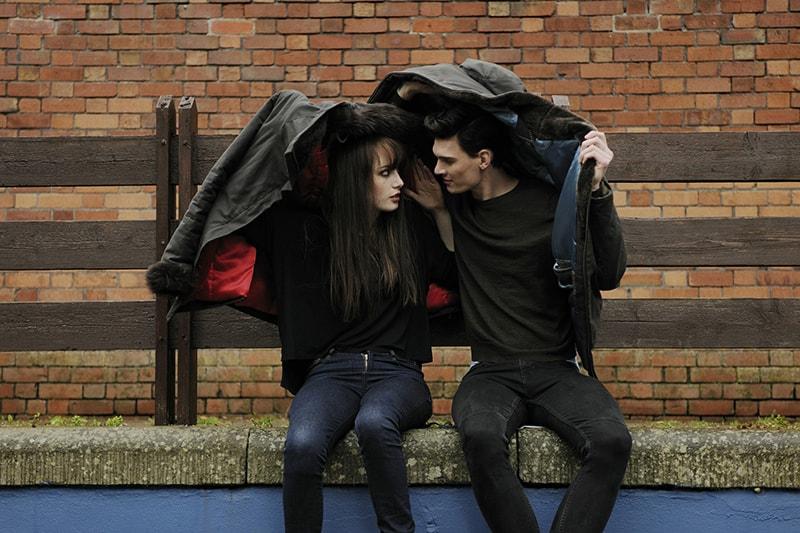 Ein Mann und eine Frau bedecken ihre Köpfe während des Regens mit Jacken