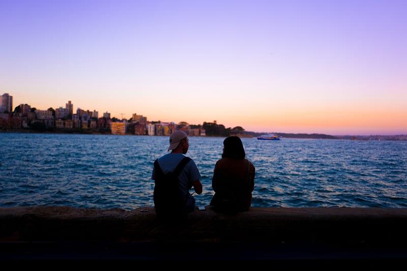 Ein Mann und eine Frau, die ein Date haben, sitzen auf dem Betonzaun und beobachten den Sonnenuntergang