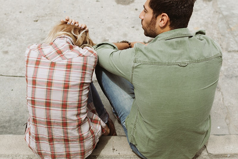 Ein Mann und eine Frau halten ihren Kopf auf dem Bürgersteig und unterhalten sich