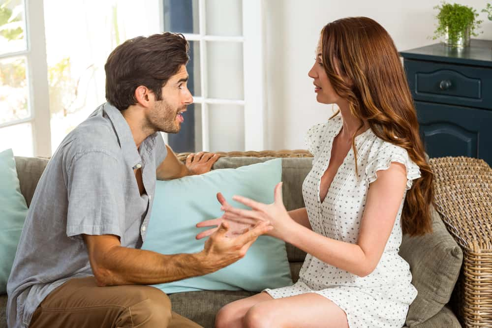 Ein Mann und eine Frau in einem weißen Kleid sitzen auf der Couch und besprechen etwas