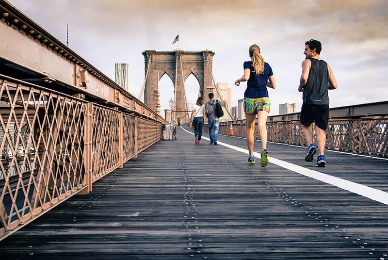 Ein Mann und eine Frau joggen zusammen an der Brücke