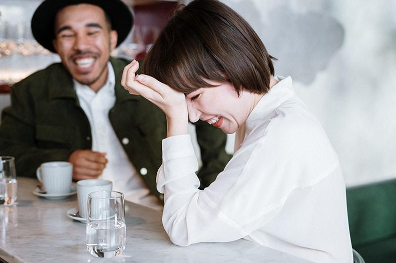 Ein Mann und eine Frau lachen während eines Dates im Café