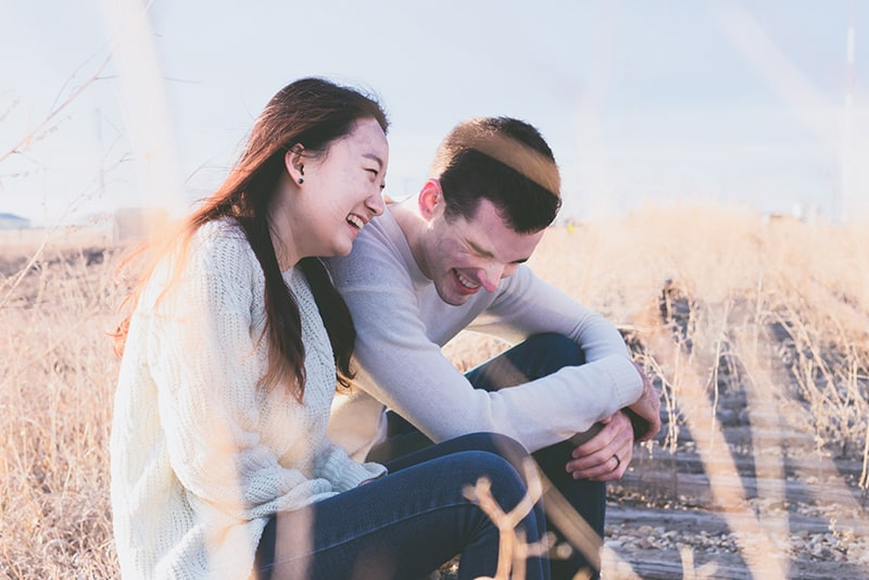Ein Mann und eine Frau lachen zusammen, während sie tagsüber auf einer alten Eisenbahn sitzen