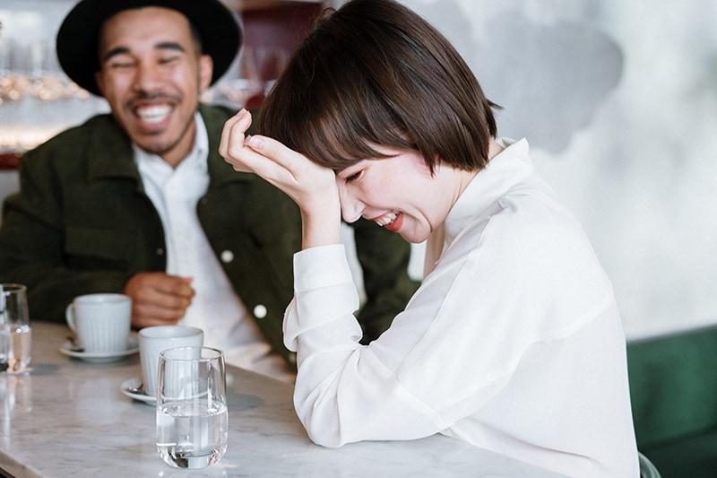 Ein Mann und eine Frau lachen zusammen, während sie im Café sitzen