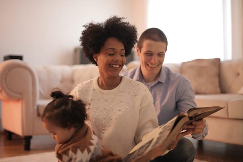 Ein Mann und eine Frau lesen ein Buch, während sie mit ihrem Kind auf dem Boden sitzen