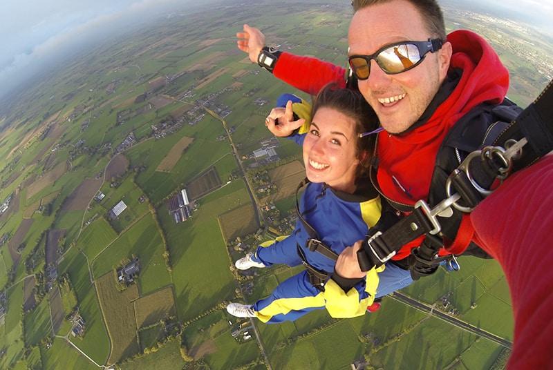 Ein Mann und eine Frau machen zusammen Fallschirmspringen