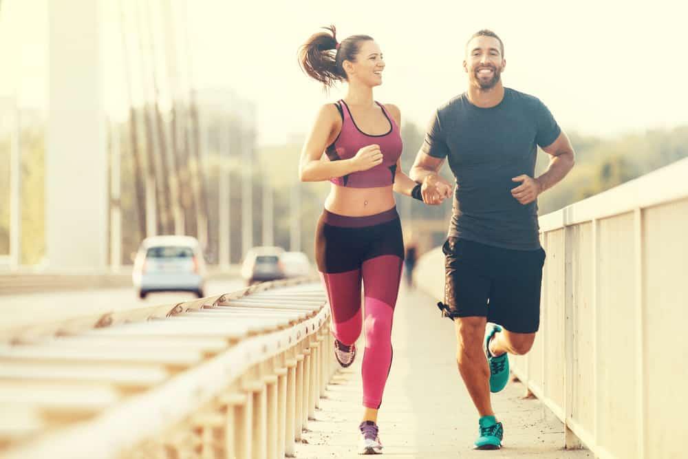 Ein Mann und eine Frau rennen lächelnd über die Brücke