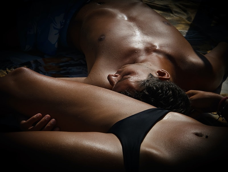 Ein Mann und eine Frau ruhen auf dem Bett in Badeanzügen