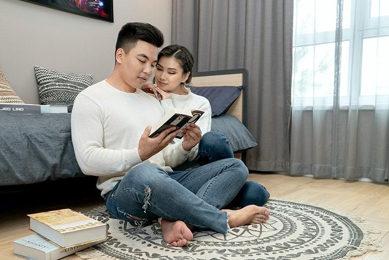 Ein Mann und eine Frau sitzen auf dem Boden, während sie ein Buch lesen