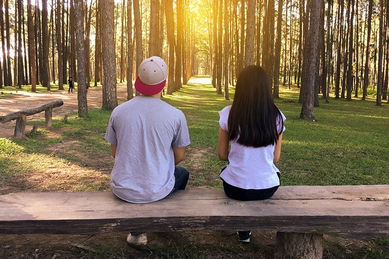 Ein Mann und eine Frau sitzen auf der Bank und zwischen ihnen stehen zwei mit Blick auf den Wald