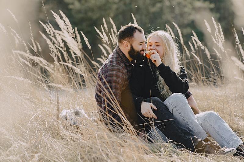 Ein Mann und eine Frau sitzen auf der Decke auf dem Feld bei einem Picknick während eines Dates