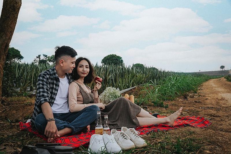 Ein Mann und eine Frau sitzen auf der roten Decke und machen ein Picknick