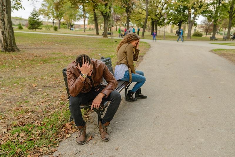 Ein Mann und eine Frau sitzen getrennt auf der Bank, während beide leiden
