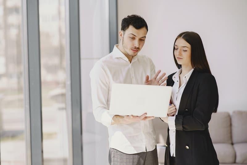 Ein Mann und eine Frau stehen und beobachten etwas auf einem Laptop