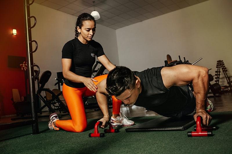 Ein Mann und eine Frau trainieren zusammen im Fitnessstudio