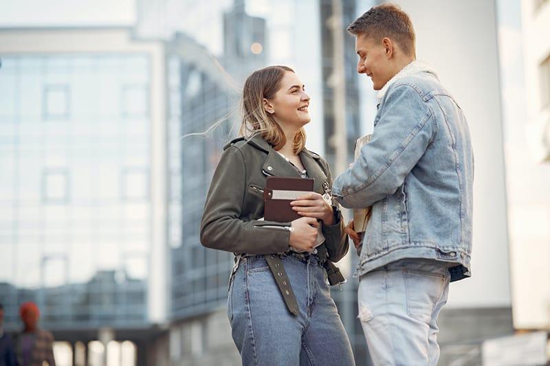 Ein Mann und eine Frau treffen sich draußen und sehen glücklich aus, sich zu sehen