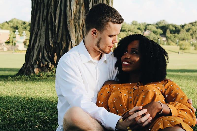 Ein Mann und eine Frau umarmen sich, während sie auf grünem Gras sitzen