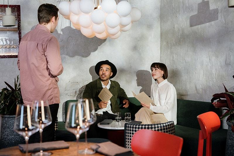 Ein Mann und eine Frau bei einem Date im Restaurant, die Essen bestellen, während der Kellner vor ihnen steht