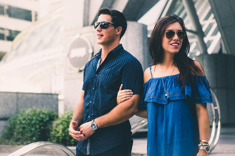 Ein Mann und seine Freundin stehen vor dem Gebäude und tragen eine Sonnenbrille