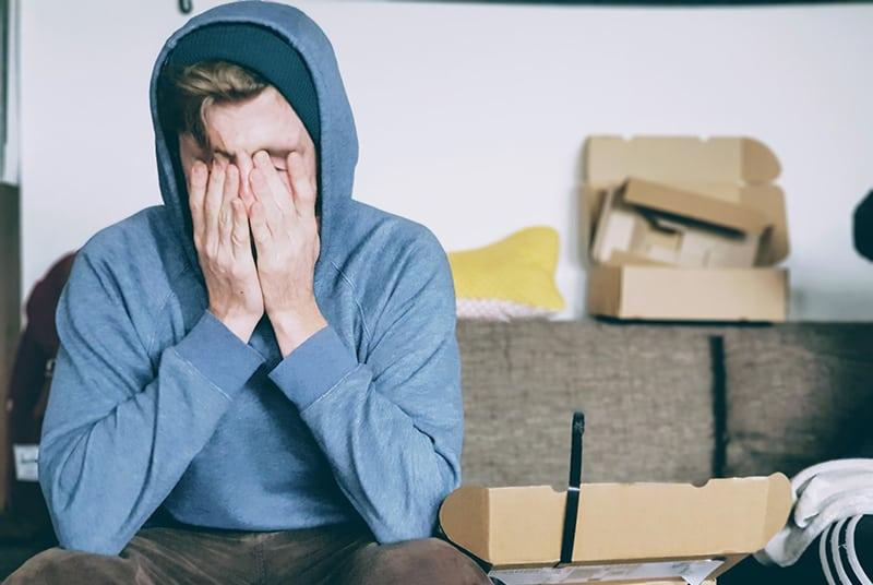Ein Mann, der unter Druck stand und sein Gesicht mit beiden Händen bedeckte, während er auf der Couch saß