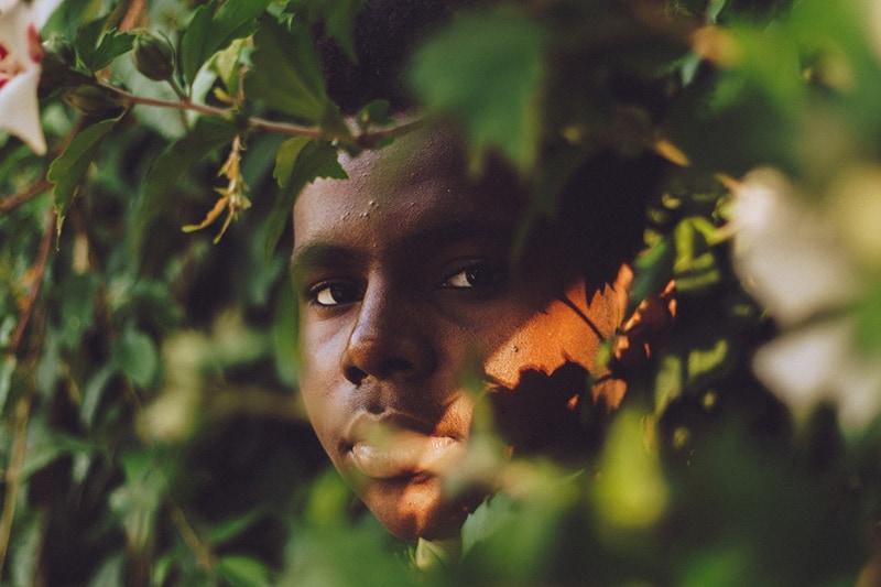 Ein Mann, der sich tagsüber hinter dem Baum versteckt