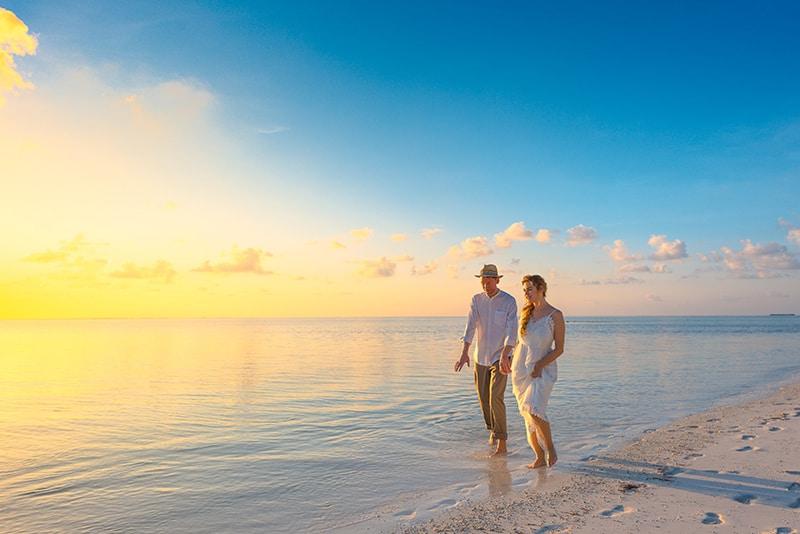 ein Paar, das während des Sonnenuntergangs an der Küste spaziert