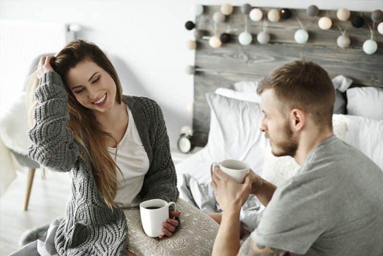 Ein Paar trinkt Kaffee im Bett