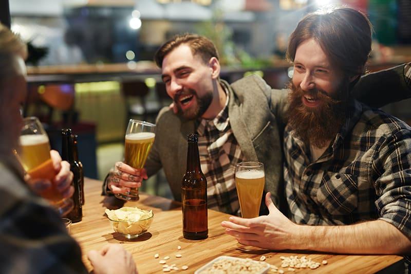 Ein betrunkener Mann umarmt seinen Freund, während er ein Glas Bier in der Bar hält