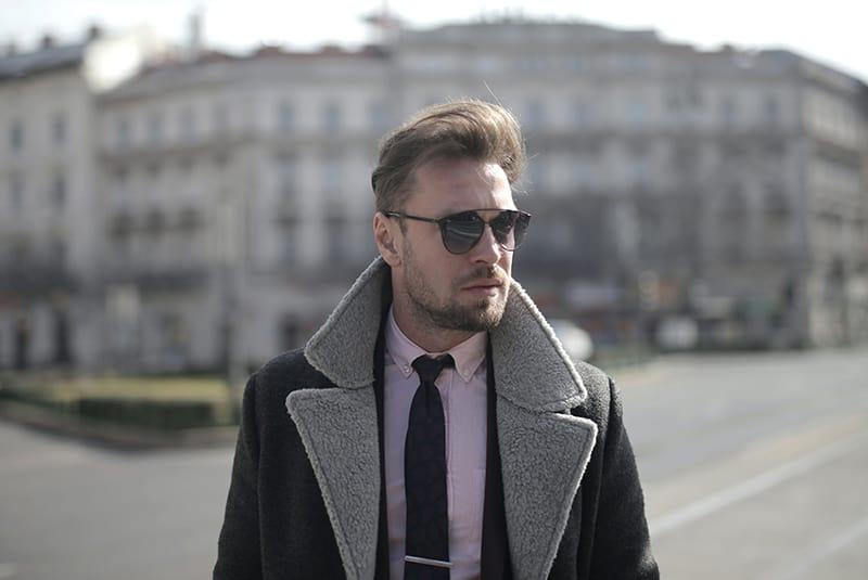 Ein ernster Mann mit Sonnenbrille in der Stadt