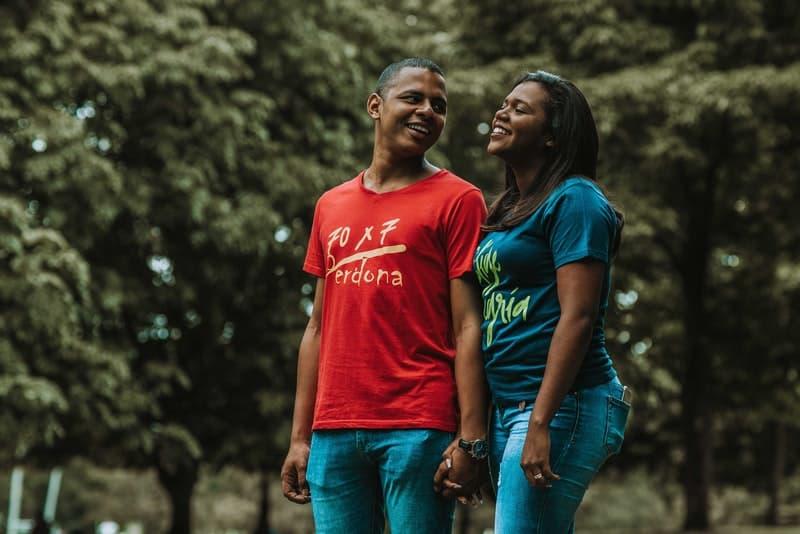 Ein lächelnder schwarzer Mann und eine lächelnde Frau gehen durch den Park