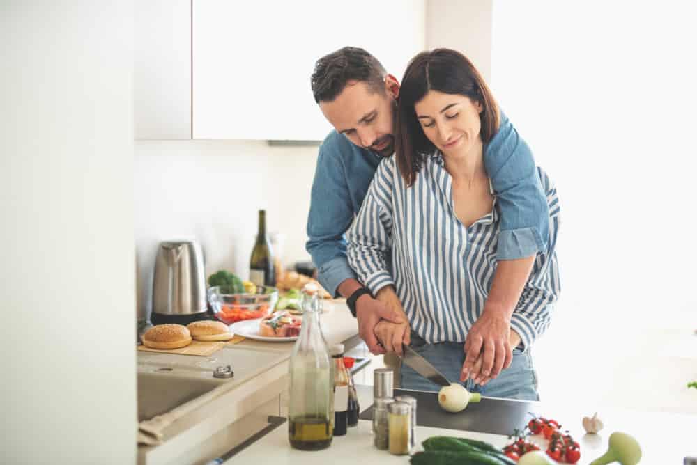Ein liebevolles Paar bereitet das Mittagessen in der Küche vor