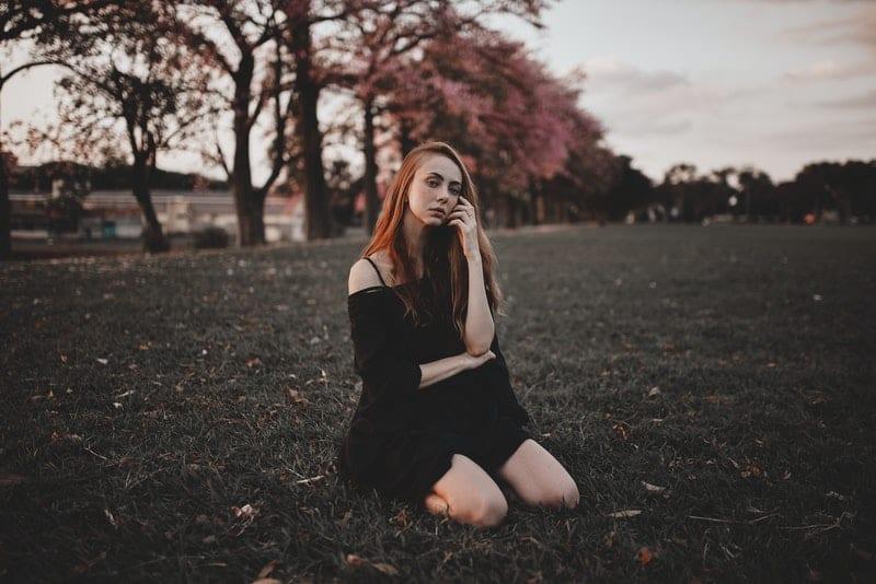 Ein rothaariges hübsches Mädchen in einem kurzen schwarzen Kleid sitzt im Gras