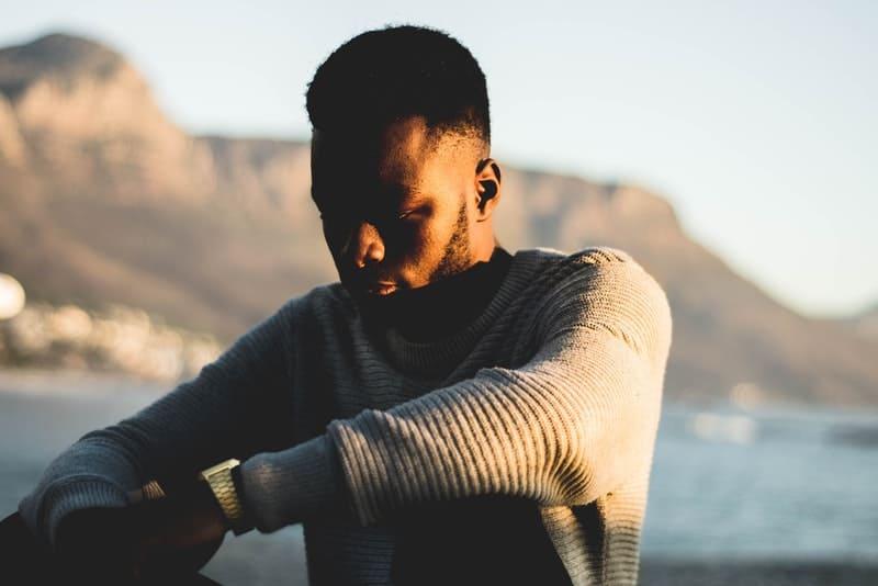 Ein trauriger schwarzer Mann in einem weißen Pullover sitzt und denkt in der Nähe des Meeres