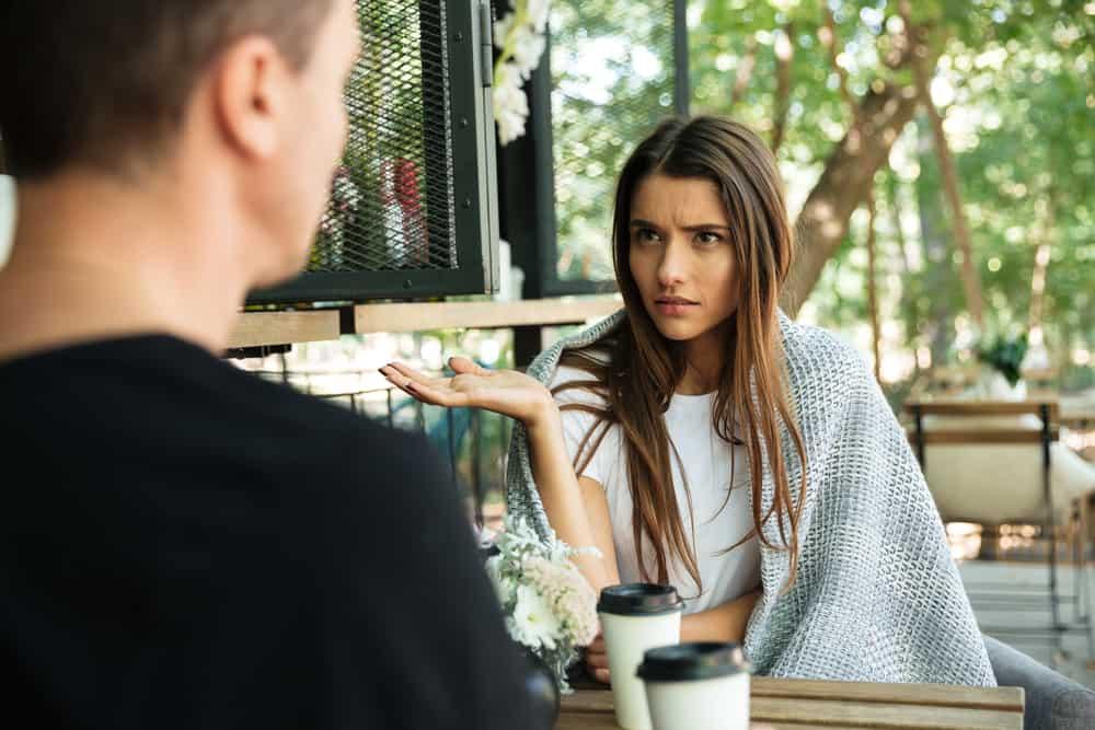 Ein verwirrtes Mädchen sitzt mit ihrem Mann in einem Café