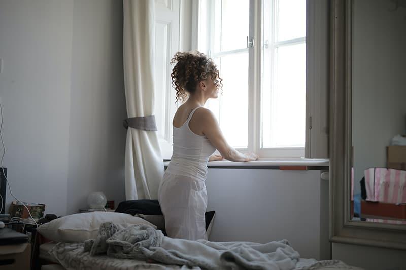 eine Frau in Nachtwäsche stehend in der Nähe des Fensters und durch es schauen