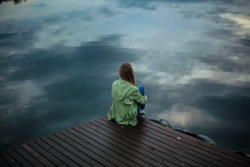 Eine Frau in einem grünen Mantel sitzt auf einem hölzernen Pier und beobachtet den See