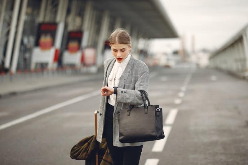 Eine Frau in einer grauen Jacke eilt irgendwohin