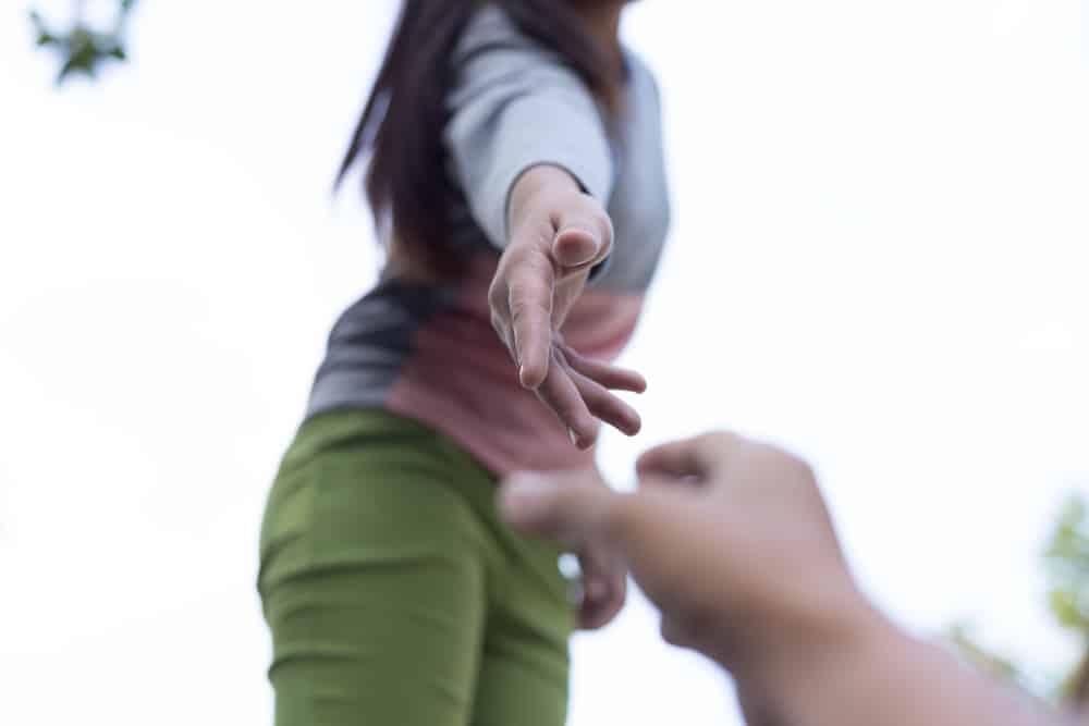 Eine Frau in grünen Hosen bietet einem Mann eine Hand zum Aufstehen