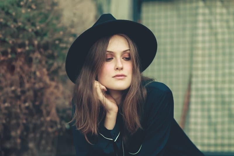 Eine Frau mit einem schwarzen Hut auf dem Kopf denkt tief über etwas nach